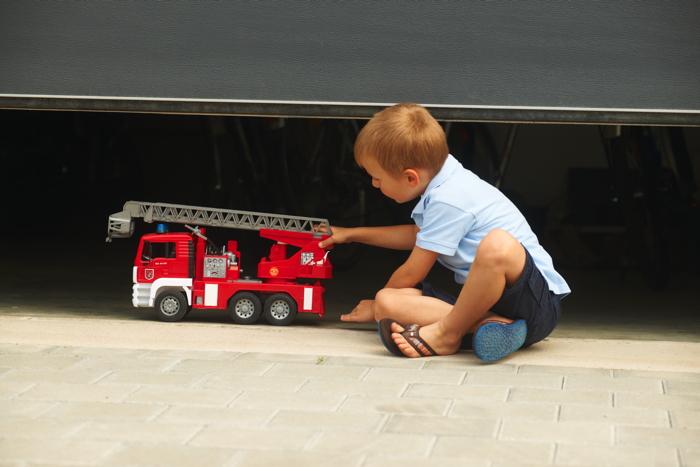 Kind spielt unter Garagentor